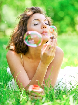 romantic young girl laying and inflating colorful soap bubbles in spring park photo