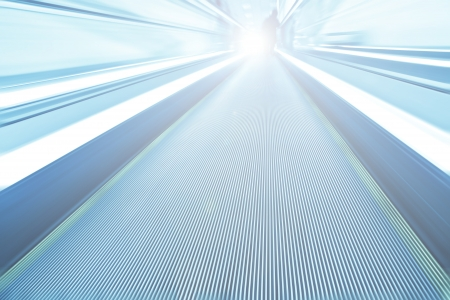 elevated walkway: Perspective wide angle view of modern light blue illuminated and spacious  high-speed moving escalator with fast blurred trail of handrail in vanishing traffic motion Stock Photo
