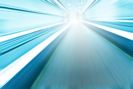 Perspective wide angle view of modern light blue illuminated and spacious  high-speed moving escalator with fast blurred trail of handrail in vanishing traffic motion Stock Photo