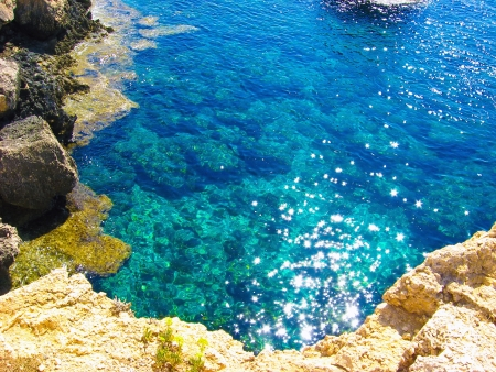 View to a rocky beautiful coast among blue bright transparent water of the sea with sky reflection in sunny day