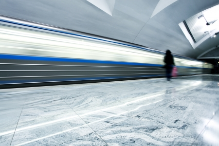 Perspective wide angle view of modern light blue illuminated and spacious public metro marble station with fast blurred trail of train in vanishing traffic motion Stock Photo