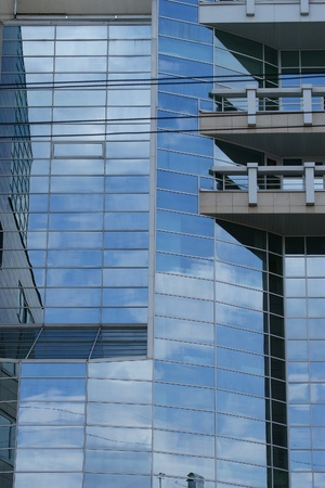 Reflection of clouds, blue sky and the other buildings in the glass windows of office building photo