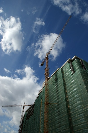 slings: Building crane at the background of a multi-storey building under construction Stock Photo