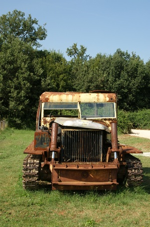 Old rusted tractor in a summer field photo