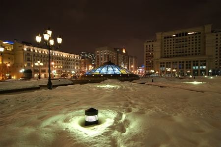 Glass cupola crowned by a statue of Saint George, holy patron of Moscow, with the Manege looming in the background , winters night, Moscow, Russia