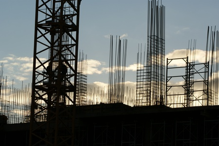 The silhouettes of construction workers, construction equipment and elements of a building under construction at Sunset photo