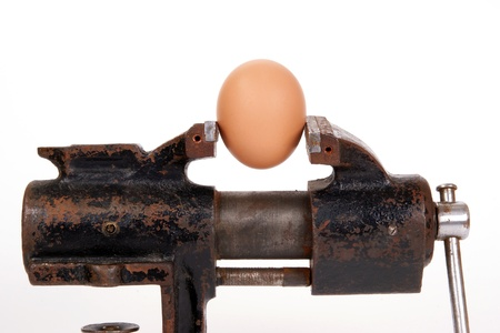 Egg trapped in the old rusty metalwork vice, on a white background photo