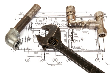 Plumbing parts and tools on the drawing, close-up
