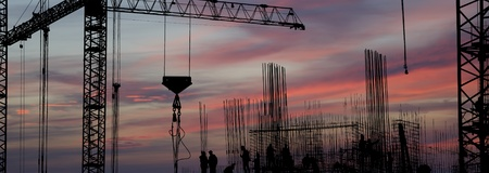 silhouettes of construction workers, construction equipment and elements of a building under construction at Sunset Stock Photo