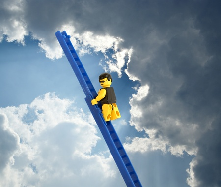 Plastic toy man on a high ladder against the sky and clouds photo
