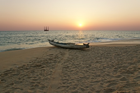 boat on the ocean shore at sunset. Kerala, India photo