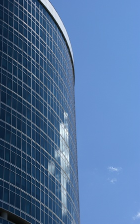 Reflection of a cloudy sky in glass wall of an office building photo