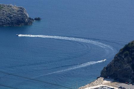Paleokastritsa, island Corfu, Ionian sea, Greece. Powerboats in the sea against coast photo