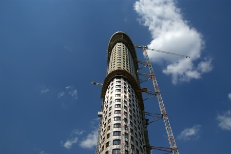 Building crane at the background of a multi-storey building under construction photo