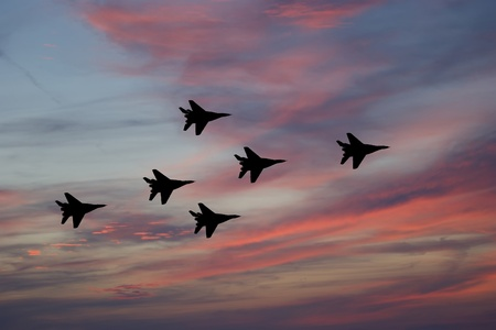 Flight of modern combat fighters on the sky background Stock Photo
