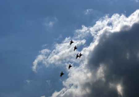 Flight of modern combat fighters on the sky background