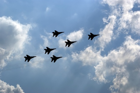 Flight of modern combat fighters on the sky background photo