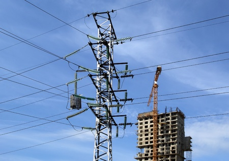 electric pylon and building crane at the background of building under construction Stock Photo - 13413820