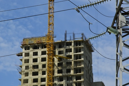 electric pylon and building crane at the background of building under construction
