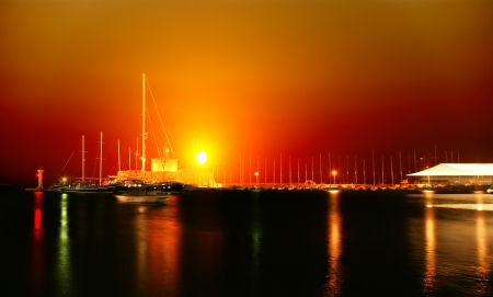 Tower of St. Nicholas in Rhodes (Greece) by night - Bluelight. Motion blur on greek flag and sail masts. Original colors. photo