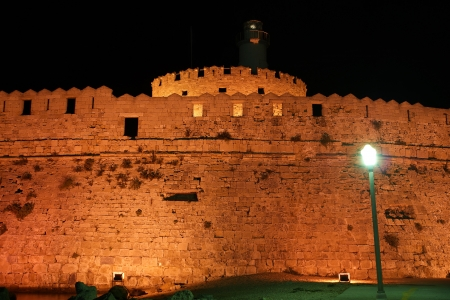 Tower of St. Nicholas in Rhodes (Greece) by night - Bluelight. Motion blur on greek flag and sail masts. Original colors.