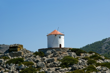 Old windmill on the shore of one of the Greek islands of the Dodecanese in the Aegean Sea, Greece photo