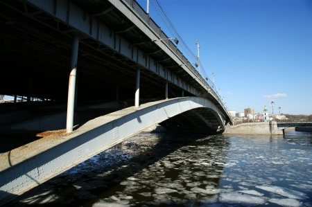 moskva river: Bolshoy Ustinsky Bridge in Moscow, Russia-- is a steel arch bridge that spans Moskva River near the mouth of Yauza River, connecting the Boulevard Ring with Zamoskvorechye district  Stock Photo