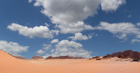 known: Wadi Rum Desert (panoramic view) also known as The Valley of the Moon is a valley cut into the sandstone and granite rock in southern Jordan 60 km to the east of Aqaba Stock Photo