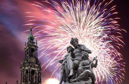 Sculpture on the Bruhl Terrace and  Hofkirche or Cathedral of Holy Trinity and holiday fireworks - baroque church in Dresden, Sachsen, Germany