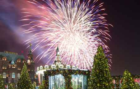 Fireworks over the Christmas and New Year holidays illumination at night, Kremlin in Moscow, Russia. Historical Museum -- inscription in Russian Stock Photo