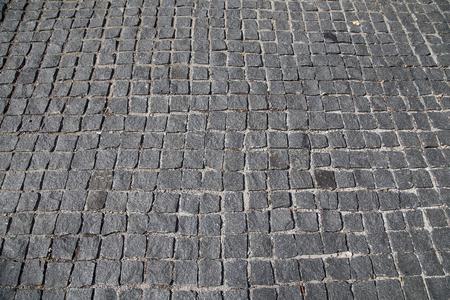 Stone pavement texture-- Granite cobblestoned pavement background. Abstract background of old cobblestone pavement (closeup)