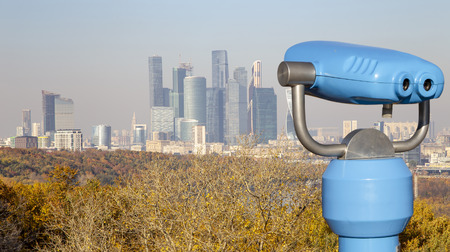 Touristic telescope viewer (binoculars) and View of the city and the complex of skyscrapers Moscow city from Sparrow Hills or Vorobyovy Gory observation (viewing) platform-- is on a steep bank 85 m above the Moskva river, or 200 m above sea level. Moscow, Russia
