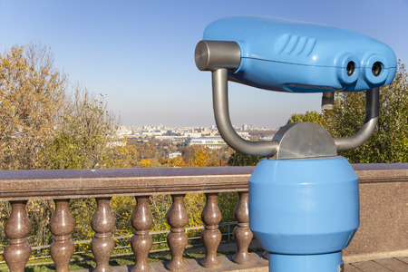 Touristic telescope viewer (binoculars) and view of central Moscow from Sparrow Hills or Vorobyovy Gory observation (viewing) platform-- is on a steep bank 85 m above the Moskva river, or 200 m above sea level. Moscow, Russia Stock Photo