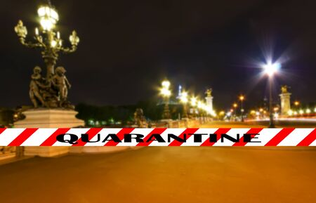Coronavirus in Paris, France. Quarantine sign on a blurred background. Concept of COVID pandemic and travel in Europe.  The Alexander III bridge at night. Foto de archivo