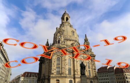 Coronavirus in Dresden, Germany. Frauenkirche ( literally Church of Our Lady). Covid-19 sign on a blurred background. Concept of COVID pandemic and travel in Europe.