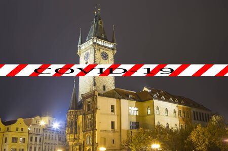 Coronavirus in Prague, Czech Republic. Old Town City Hall. Covid-19 sign. Concept of COVID pandemic and travel in Europe.