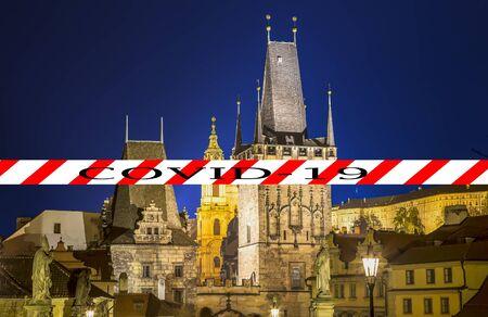 Coronavirus in Prague, Czech Republic. Mala Strana Bridge Tower at Charles Bridge. Covid-19 sign. Concept of COVID pandemic and travel in Europe.
