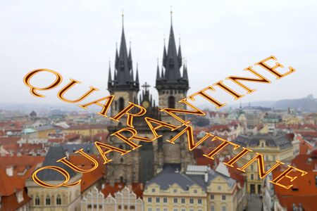 Coronavirus in Prague, Czech Republic. The gothic Church of Mother of God in front of Tyn. Quarantine sign on a blurred background. Concept of COVID pandemic and travel in Europe.