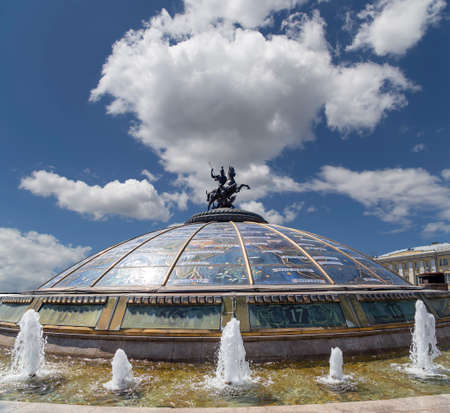 Manege Square (Glass cupola crowned by a statue of Saint George, holy patron of Moscow) on a cloud background. Inscription in Russian: names of famous cities in the world. Moscow, Russia