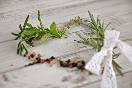 Heart made of different herbs and spices: rosemary, thymus, mint and pepper on white background photo