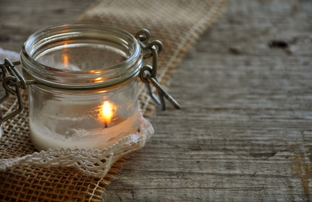 wood burning: white candle in the jar on jute ribbon and grey wood
