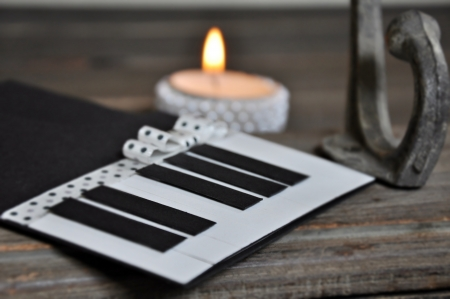 Piano made from paper with candle in the background photo