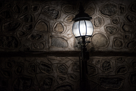 Old lamp lighting a spot on a stone wall