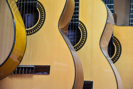 Closeup of guitars lined up for sale in a music store