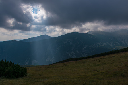 Beam of light shining through a hole in the clouds over a mountain landscape