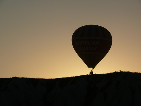 Silhouette of a hot air balloon over a mountain in the sunrise