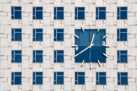 identical: Clock on a contemporary building facade with mulptiple identical windows