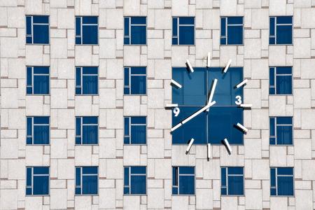 Clock on a contemporary building facade with mulptiple identical windows
