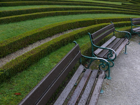 A row of benches forming an arch in a park during a drizzling rain