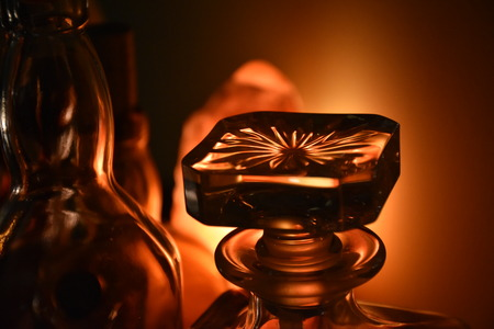 Closeup of a glass cap of a whiskey bottle, softly lit from tha back